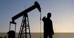Oil pump and worker at dusk